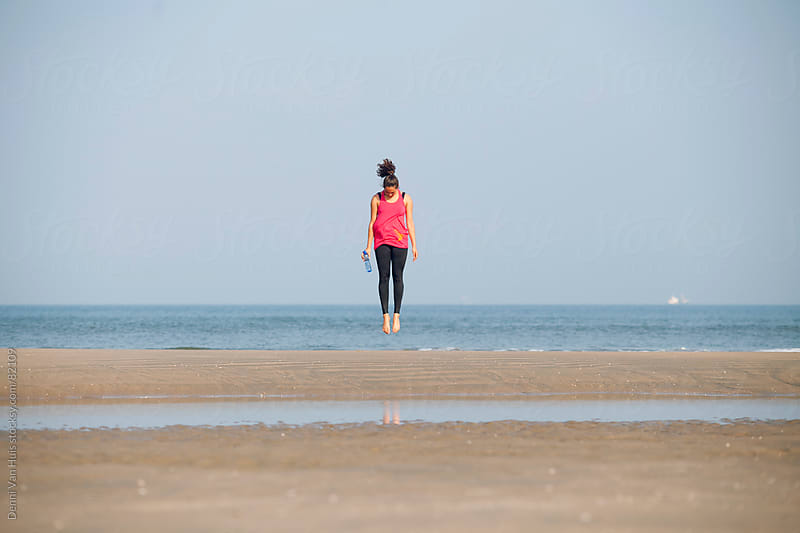 Healthy young woman jumping on the beach during her workout  by Denni Van Huis for Stocksy United