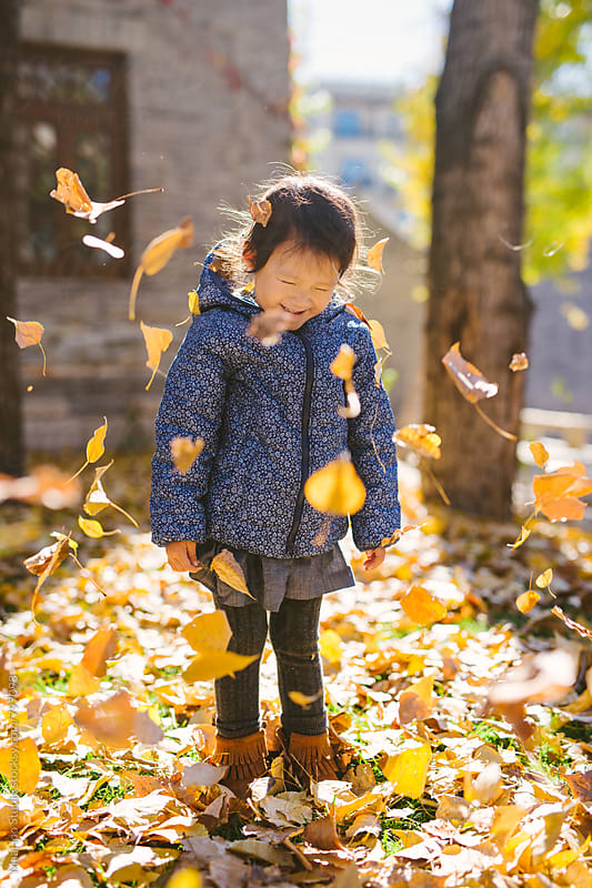 Toddler girl playing with yellow leaves in autumn park by MaaHoo Studio for Stocksy United