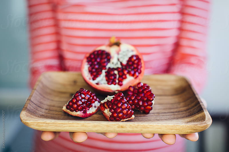 Female hands holding wooden plate with pomegranate by Zocky for Stocksy United