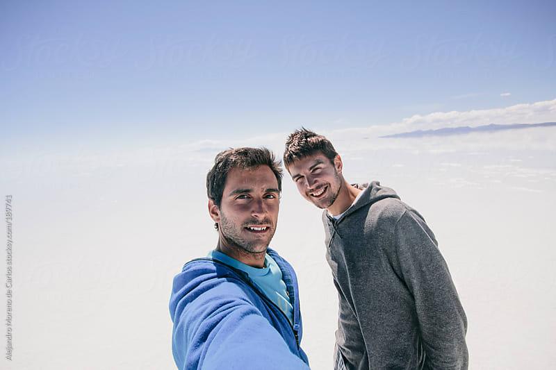 Two friends taking selfie on Uyuni salt falt during adventure travel by Alejandro Moreno de Carlos for Stocksy United