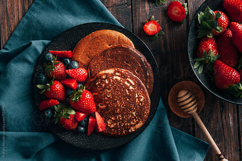 Pancakes with strawberries and blueberries by Nataša Mandić for Stocksy United