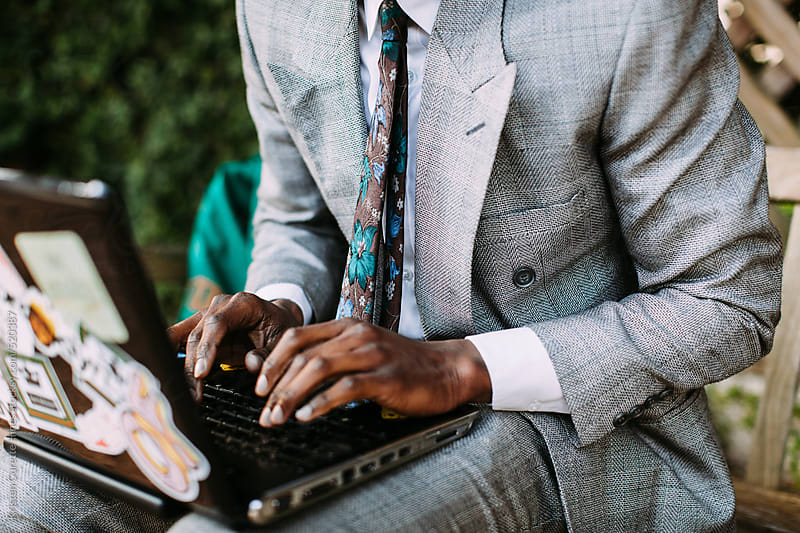 Close up of a man working on a laptop outdoors by Kristen Curette Hines for Stocksy United