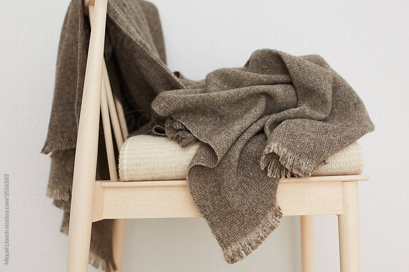Hand made wool blankets on a wooden chair by Miquel Llonch for Stocksy United