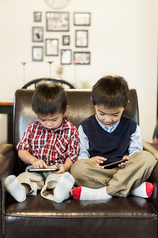 Asian kids playing game at home on the cell phones  by Suprijono Suharjoto for Stocksy United