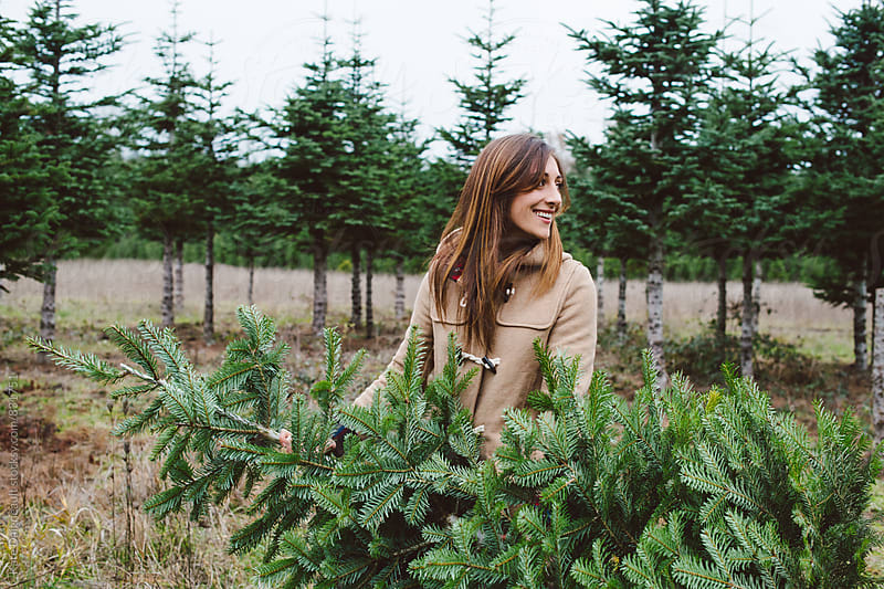 Beautiful young woman carry christmas tree in wooded field in the winter. by Kate Daigneault for Stocksy United