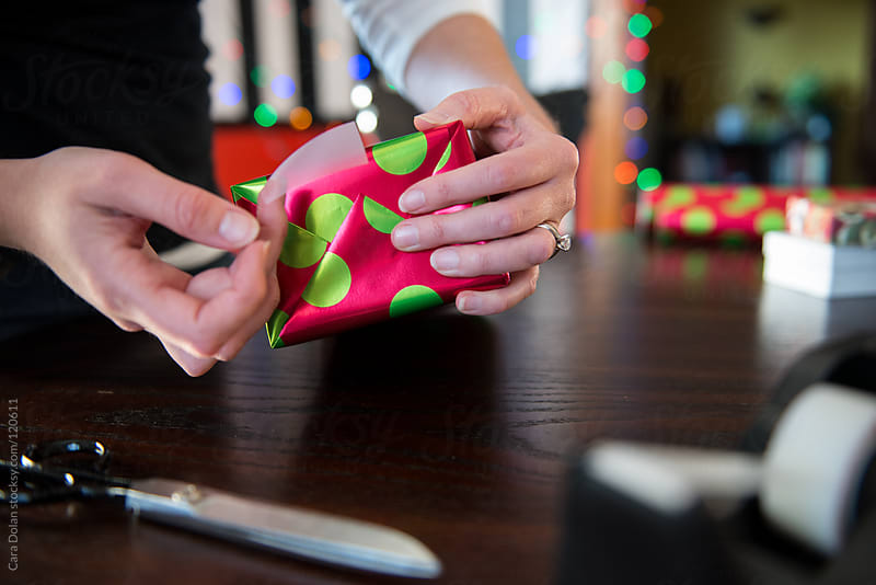 Christmas gifts are wrapped in colorful paper by Cara Dolan for Stocksy United