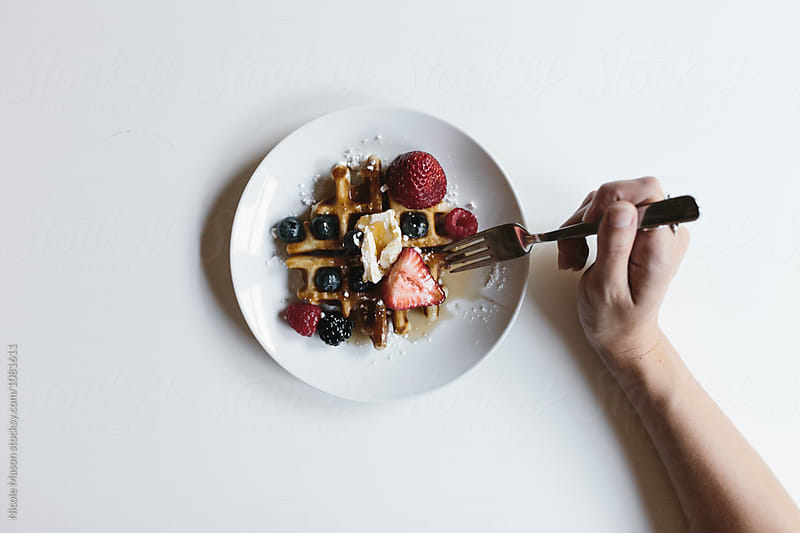 overhead shot of person eating waffle with berries and butter by Nicole Mason for Stocksy United