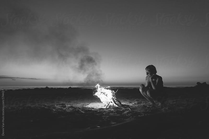 Woman enjoying the warmth of a bonfire on the beach under the stars. by Denni Van Huis for Stocksy United
