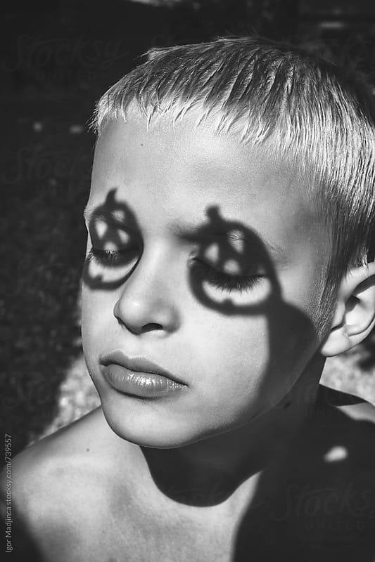 blond boy with pumpkin shadow on the eyes, Halloween by Igor Madjinca for Stocksy United