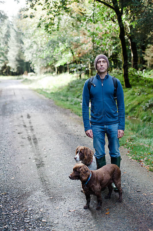 Man standing in a wood with two dogs by Suzi Marshall for Stocksy United
