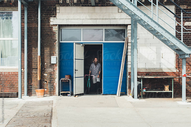 Millennial Hipster Leaving Industrial Building With Fixed Gear Bicycle by Julien L. Balmer for Stocksy United