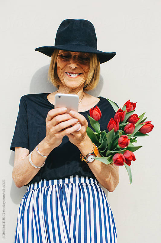Stylish senior woman holding red tulips using her phone outside.  by BONNINSTUDIO for Stocksy United