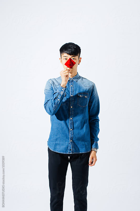 Portrait of an asian man holding a red glass in front his face. by BONNINSTUDIO for Stocksy United