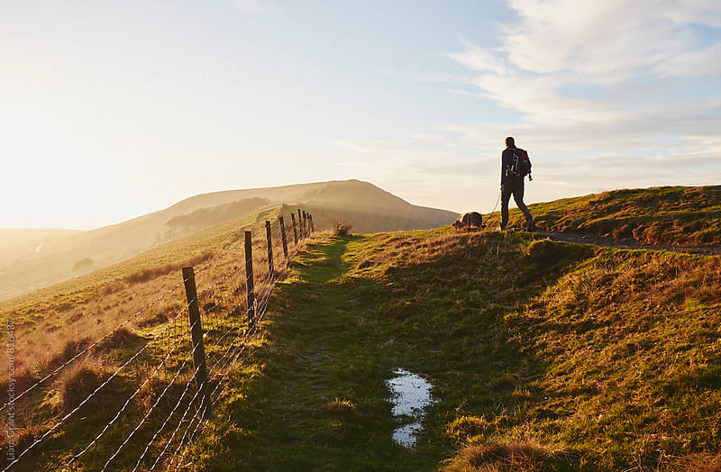 Male walking his dog on Rushup Edge at sunset. Derbyshire, UK. by Liam Grant for Stocksy United