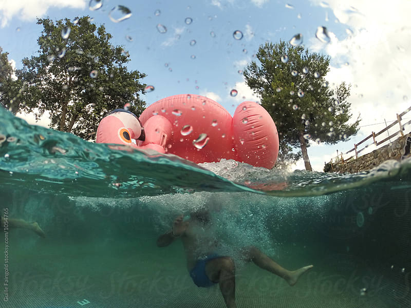 Underwater shot of person jumping in pool with flamingo inflatable by Guille Faingold for Stocksy United