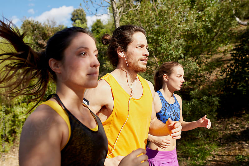 Man With Female Friends Jogging On Sunny Day by ALTO IMAGES for Stocksy United