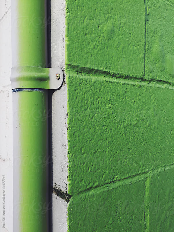 Detail of painted green corner of building and gutter pipe by Paul Edmondson for Stocksy United
