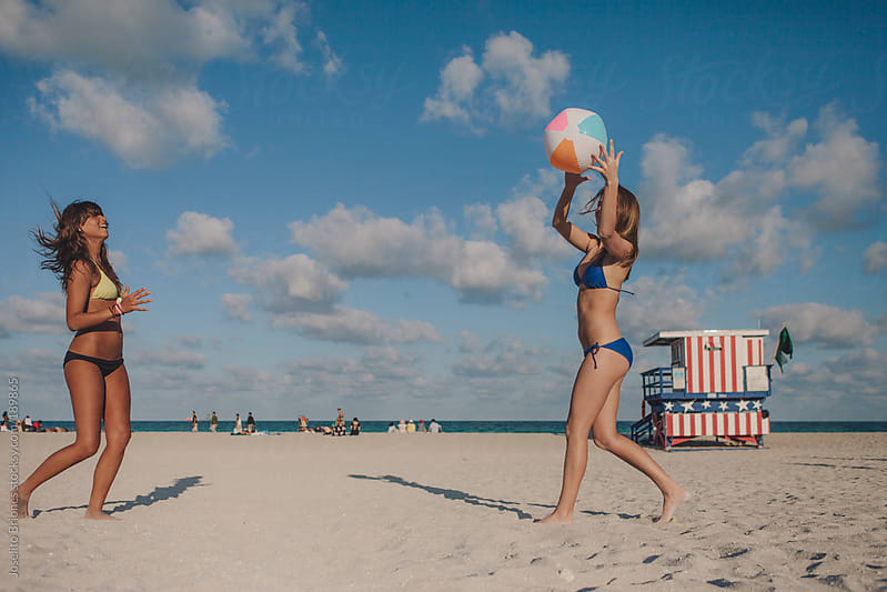 Young Women Friends In Swimsuit Playing Catch with Beach Ball in the Summer  in Miami by Joselito Briones for Stocksy United