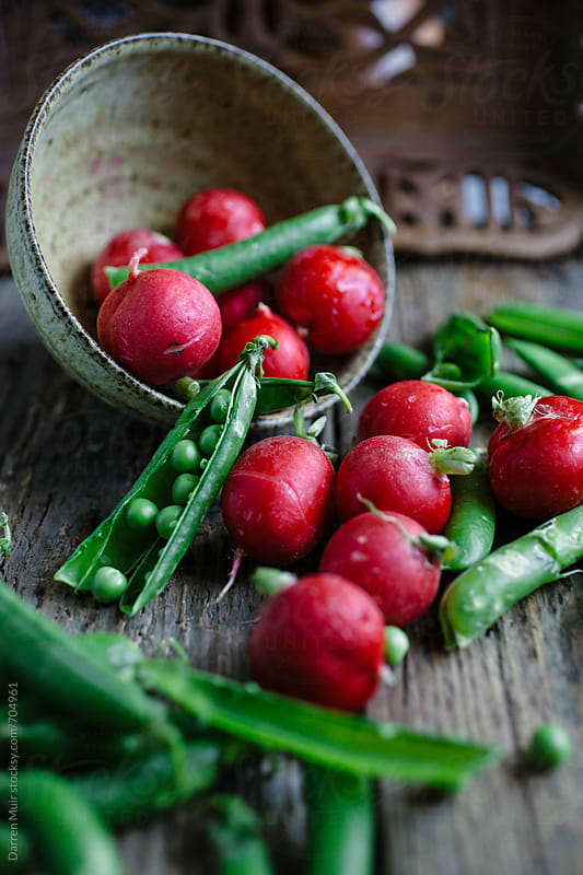 Peas and radishes spilling out of a bowl onto a wood table. by Darren Muir for Stocksy United