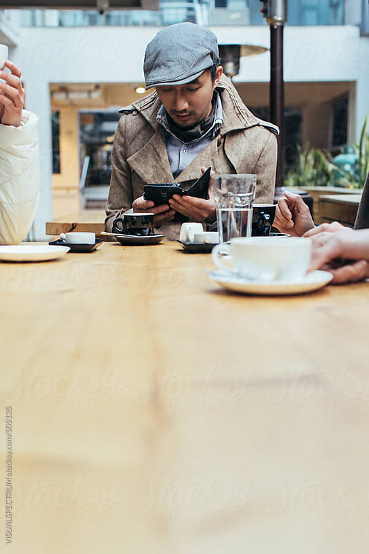 Well-Dressed Young Asian Man Sitting on Restaurant Terrace and Looking Down at Cellphone by VISUALSPECTRUM for Stocksy United