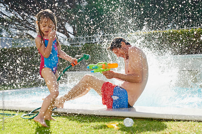 family having a wild wet fun water fight  by Aila Images for Stocksy United