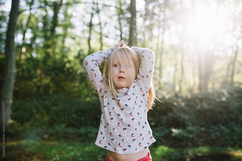 Little Girl Stands on the Oustkirts of the Woods in the Evening Light by Amanda Voelker for Stocksy United