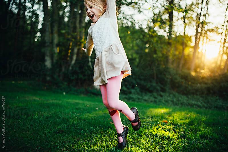 Little girl joyfully jumps in the light of the setting sun by Amanda Voelker for Stocksy United