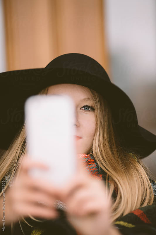 blond woman takes a selfie with the cell phone  by Vesna for Stocksy United