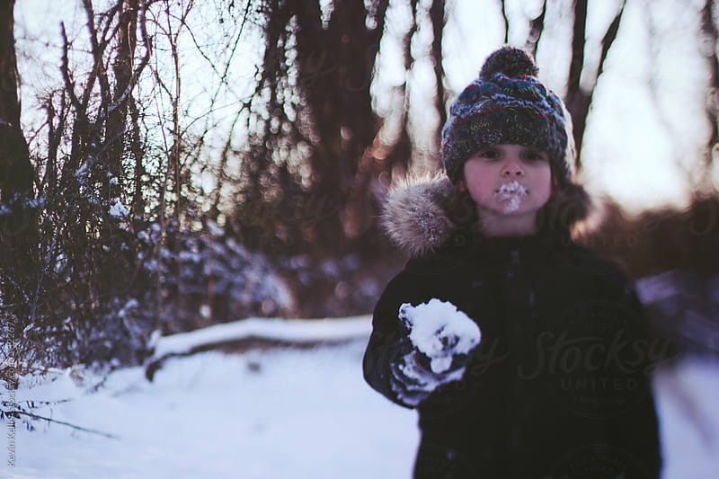 Young Boy Holding a Snowball with Snow on Mouth by Kevin Keller for Stocksy United