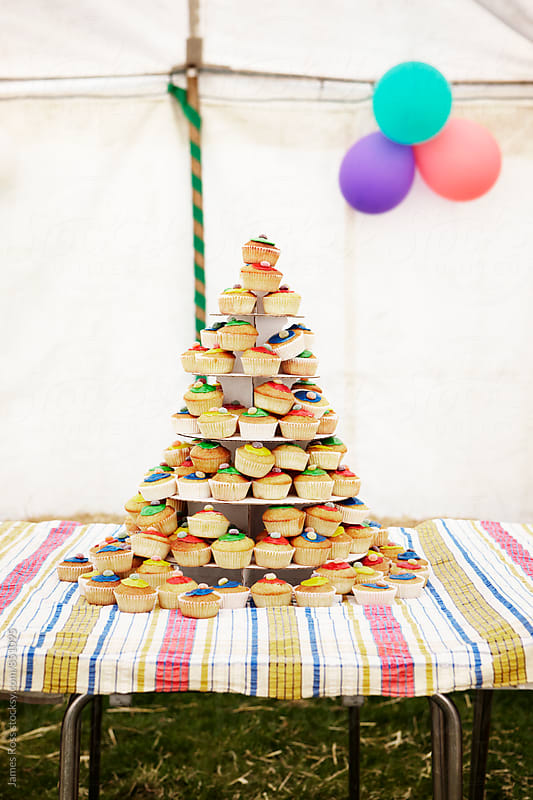 A stack of cupcakes inside a marquee by James Ross for Stocksy United