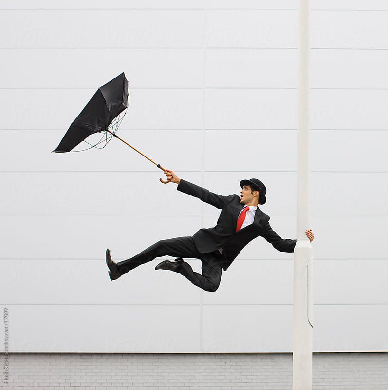 Businessman wearing bowler hat carrying umbrella by Hugh Sitton for Stocksy United