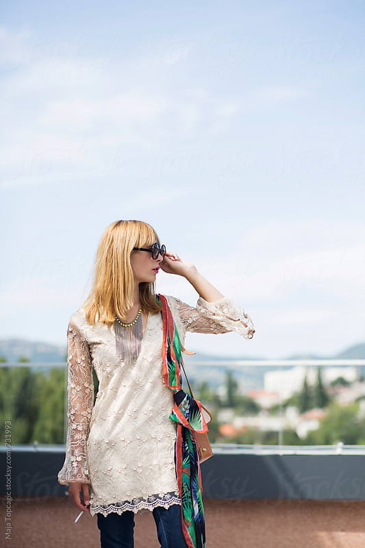 Young beautiful blond woman on a rooftop by Maja Topcagic for Stocksy United