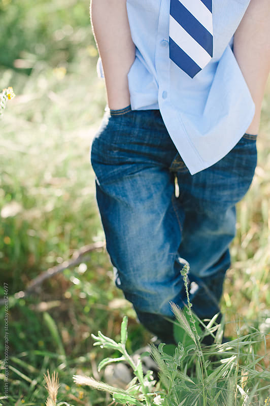 Bottom half of young boy with hands in pocket by Kristin Rogers Photography for Stocksy United