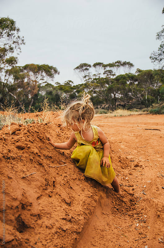 Little girl playing with bright red dirt by Dominique Chapman for Stocksy United