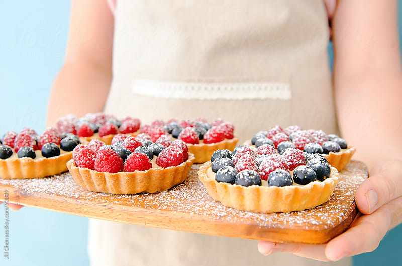 Wooden platter of mixed berry tarts by Jill Chen for Stocksy United