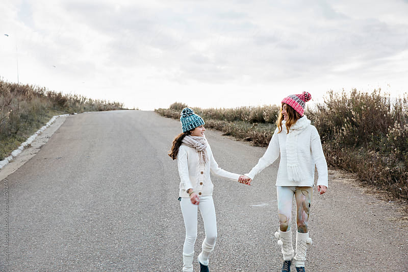 Mother and daughter walking together hand in hand by Beatrix Boros for Stocksy United