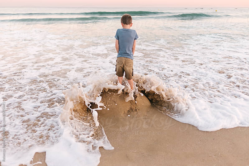 Waves surround and destroy a sandcastle with a child standing on it by Rebecca Spencer for Stocksy United