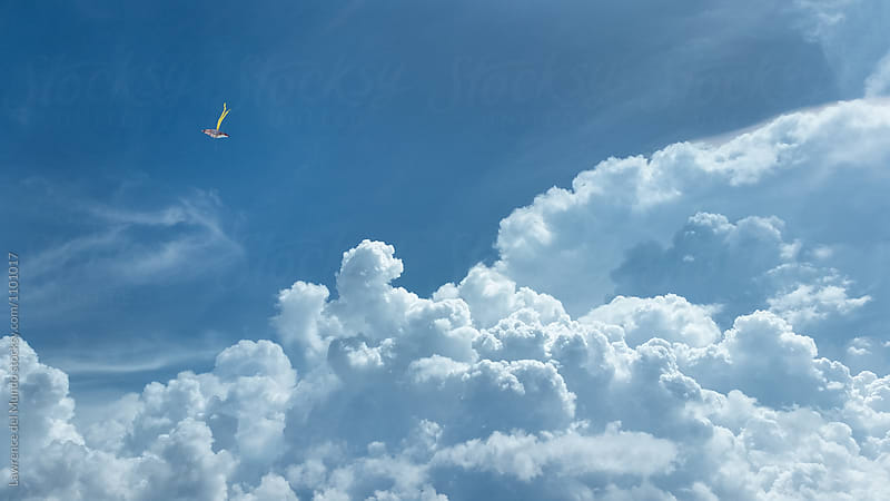 A kite, blue skies, and some majestic cloud formation.  by Lawrence del Mundo for Stocksy United