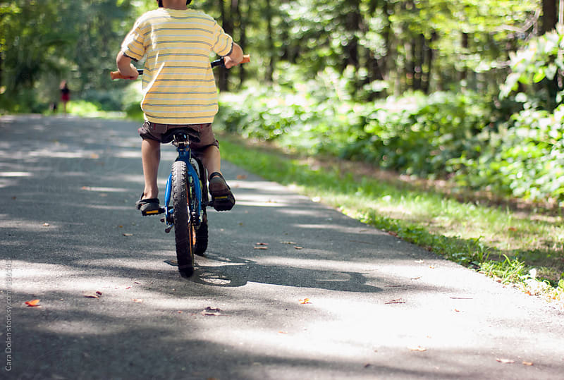 Boy riding his bicycle on a public bike path by Cara Dolan for Stocksy United