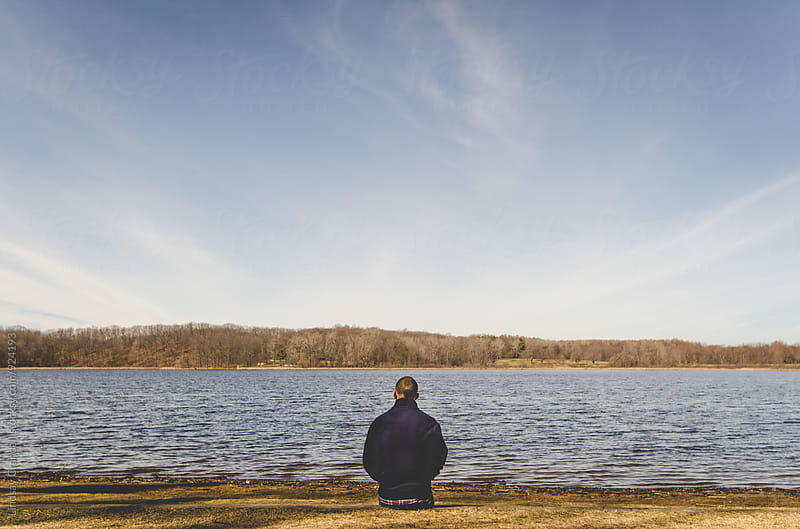 Man sitting in front of a body of water by Lindsay Crandall for Stocksy United