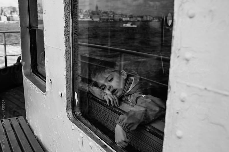 Black and white of boy gazing drowsily at the Istanbul skyline as he crosses the Bosphorus by ferryboat. by Julia Forsman for Stocksy United
