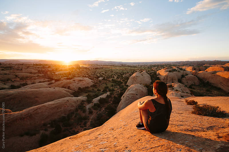 A girl watching the sun set on the top of a rock in Utah after a run by Gary Parker for Stocksy United