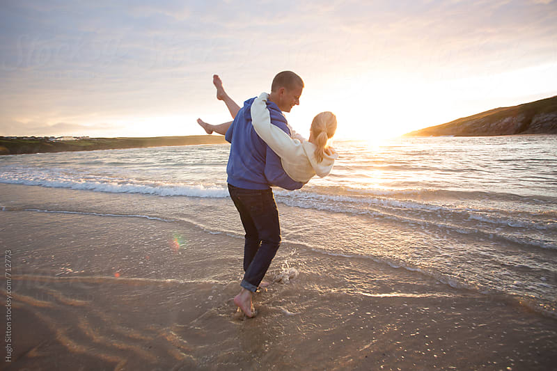 Couple on beach at sunset. by Hugh Sitton for Stocksy United