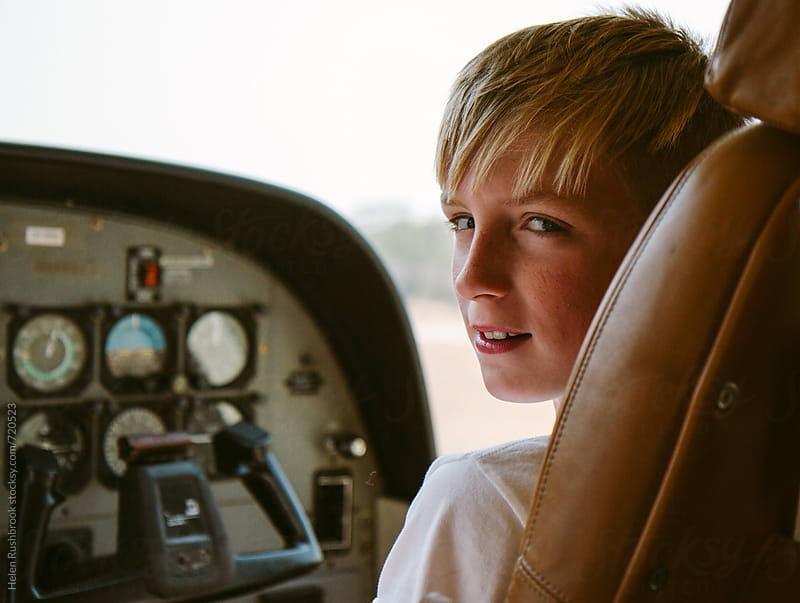 Teenage boy in the co-pilot's seat of a light aircraft by Helen Rushbrook for Stocksy United