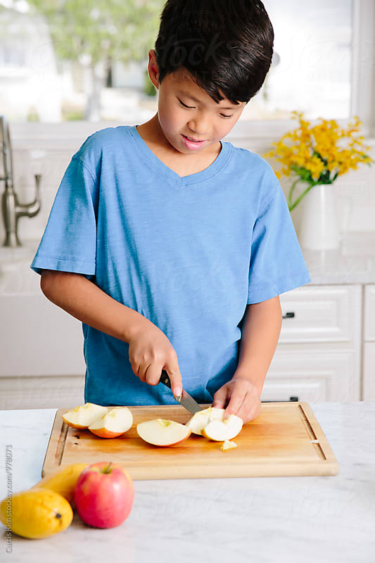 Young boy slicing up apples by Curtis Kim for Stocksy United
