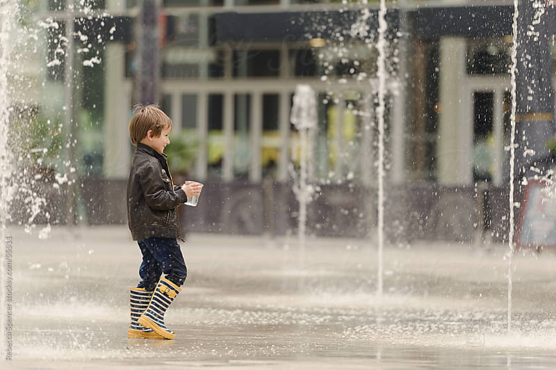 Boy playing with sprayground fountains.  by Rebecca Spencer for Stocksy United