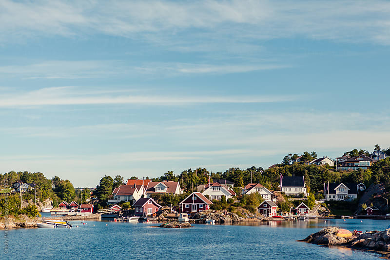 Seaside cottages and boat houses along the coast of Norway on a summer day by Cindy Prins for Stocksy United