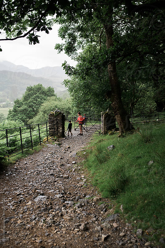 three kids on a walk in the Welsh mountains by Léa Jones for Stocksy United
