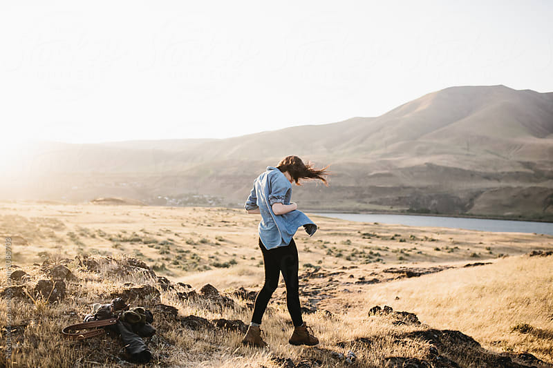 woman standing in windy field with mountains at sunset by Nicole Mason for Stocksy United