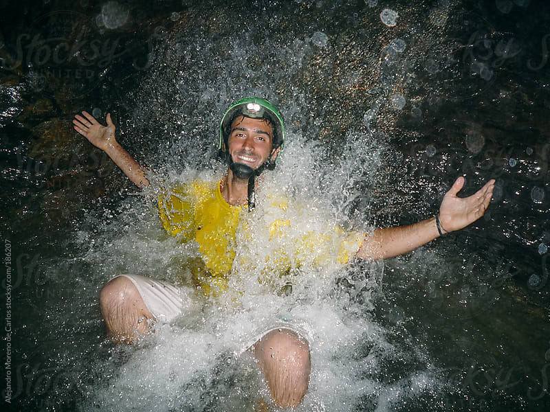 Spelunker man under a waterfall on an underground river inside a cave by Alejandro Moreno de Carlos for Stocksy United